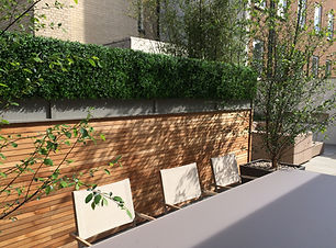 Garden table in front of cedar slatted screen and artificial hedging