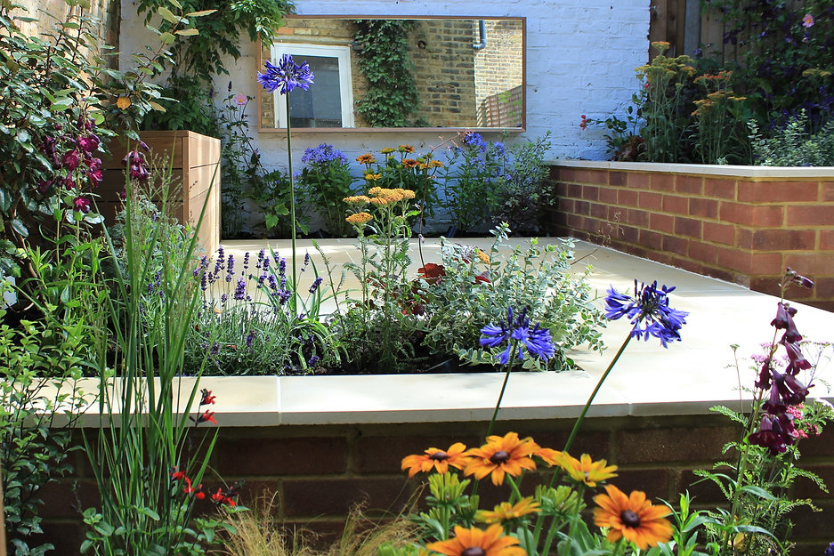 Colourful small garden with a wall mounted mirror and pretty flowers next to sawn sandstone paving