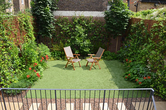 Small garden surrounded by evergreen climbing plants on trellis, with artificial lawn
