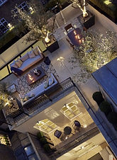 Garden on a roof terrace tastfully lit up at night, showing expensive outdoor sofas in a lounging area formed of limestone paving.
