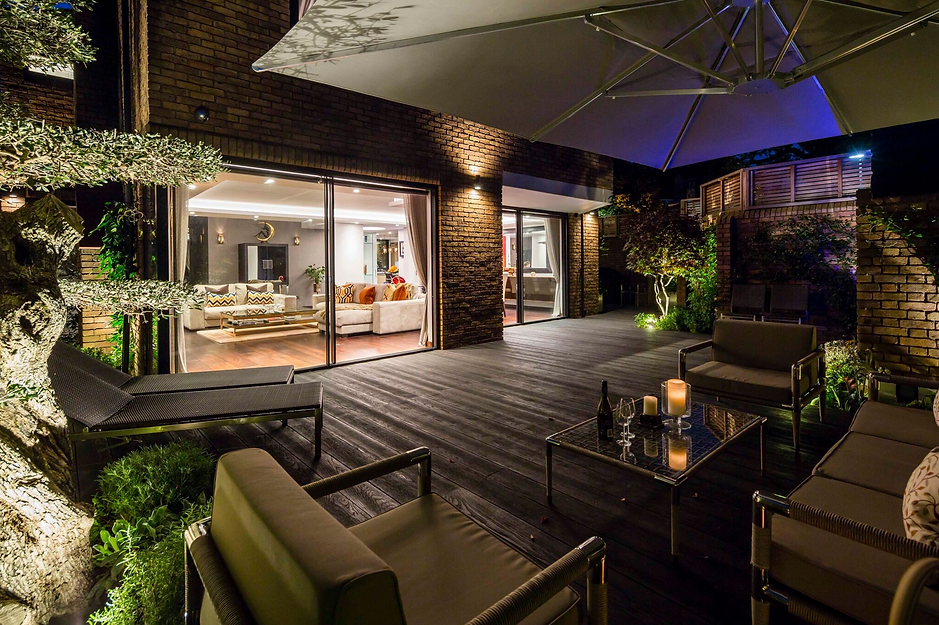 Stylish decked rear garden with expensive garden furniture, at night with garden lighting