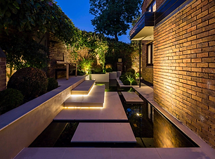 Front garden with large shallow contemporary pool, with stepping stones and lighing