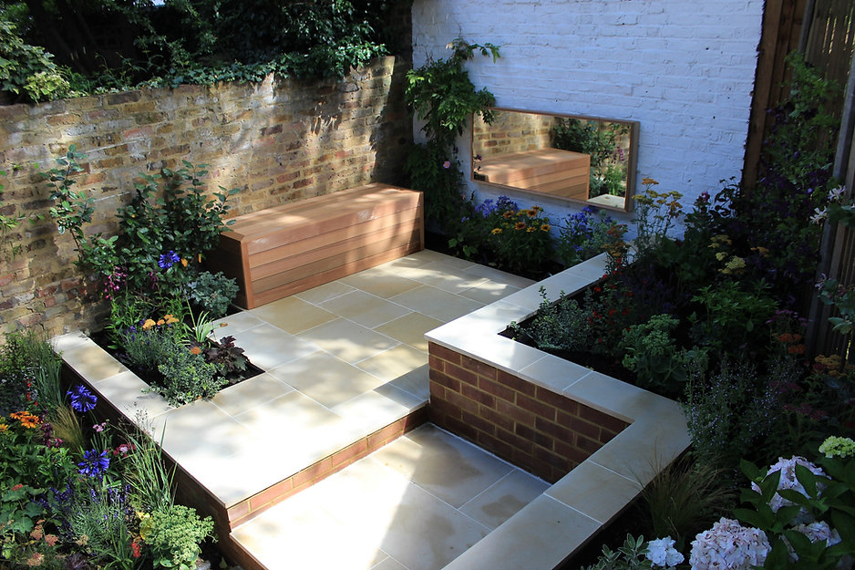 Bespoke-cedar-bench-in-a-small-andstone-paved-city-garden-surrounded-by-reclaimed-brick-walls-and-colourful-planting
