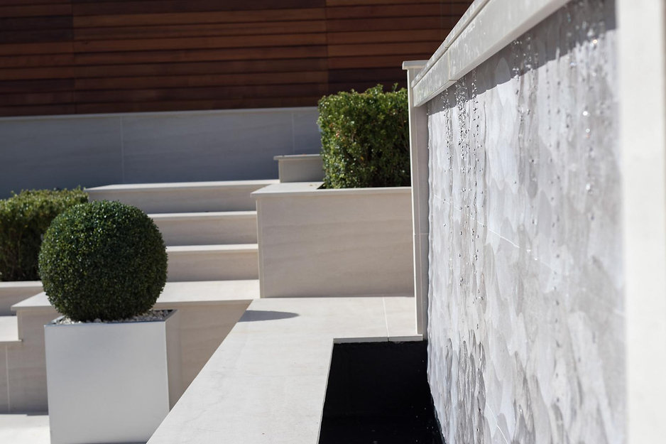 close up of a porcelain tiled water wall in a white paved contemporary garden