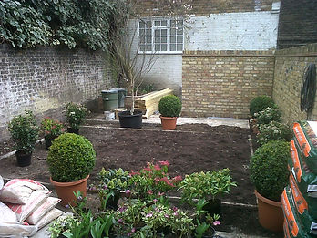 A walled small garden being planted on an overcast day
