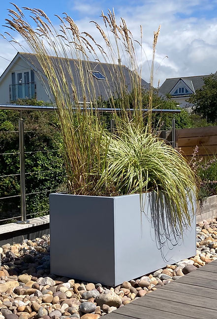 Powder-coated metal planter in RAL 7001, planted with tall grasses, on a roof terrece of cobble and deck, with blue skies.