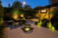 Chic front garden, lit up at night, with water feature chalice in the centre of large porcelain paving, surrounded by clipped buxus balls