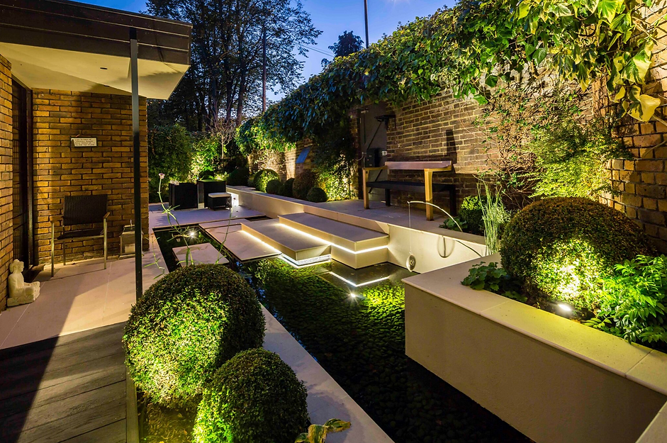 Porcelain garden steps crossing a shallow pool, with clipped buxus balls and rendered raised beds