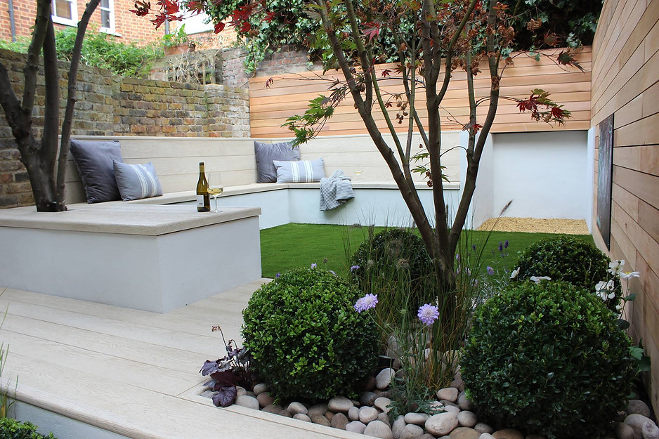 Large built-in corner bench in a small city garden, with artificial grass and Millboard decking