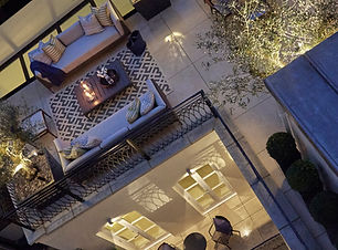 High end roof terrace lit up at night with outdoor sofas and olive trees