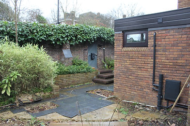 Garden in need of renovation, with broken slate paving and overgrown shrubs
