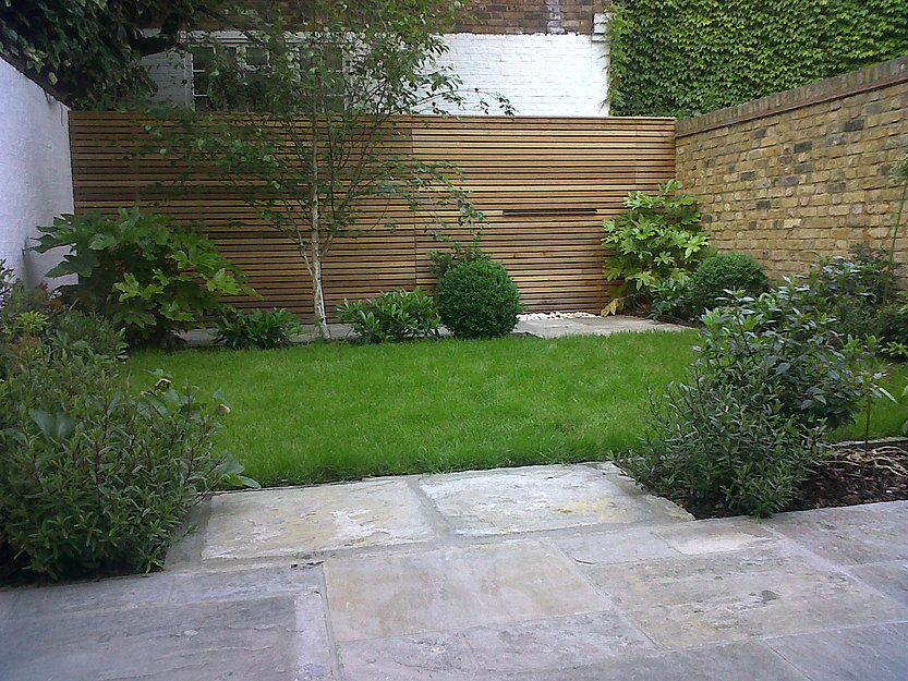Stone patio leading to a lush green lawn in a small garden. Designed with a slatted cedar screen, water feature and evergreen planting