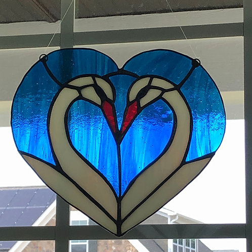 blue stained glass heart with two swans facing each other, making a second heart