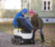 Two kids on the street check out Starship's food delivery robot