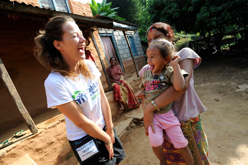 A Habitat for Humanity volunteer with the family she is helping to build their new home. Over 250 international volunteers worked on building new homes in Pokhara, Nepal. 2010