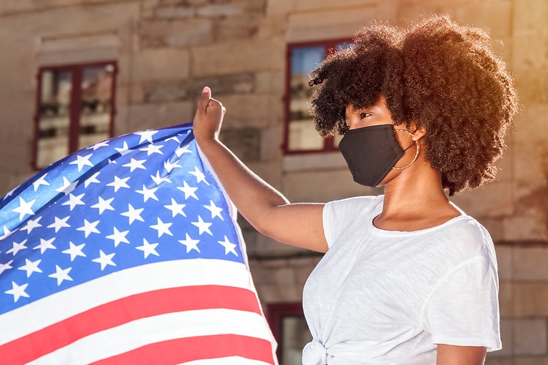 Black woman with mask and afro hair hold