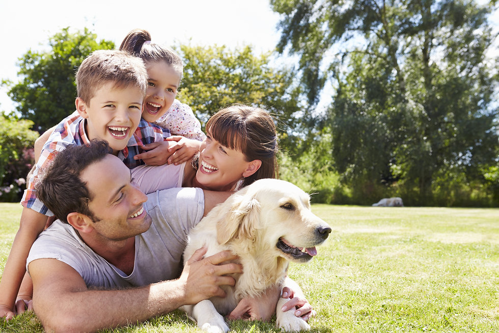Family Relaxing In Garden With Pet Dog.j