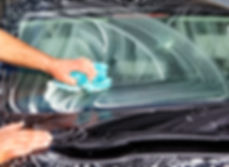 Man washing a black car with a cloth.jpg