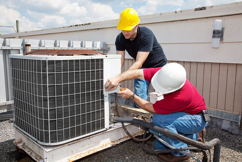 Two Maintenance Workers on Building Working on Air Condition