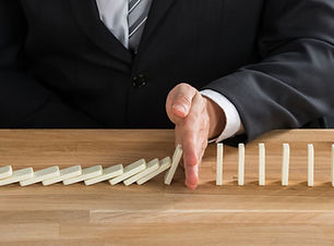 businessman-stopping-dominoes-from-falli