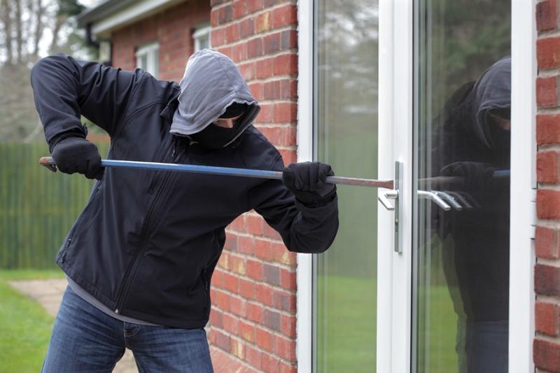 bigstock-Burglar-breaking-into-a-house-4