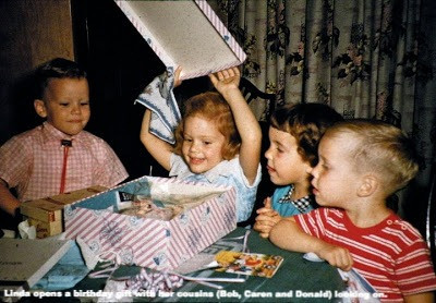 Linda opens a birthday gift with her cousins (Bob, Caren and Donald) looking on.