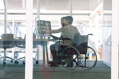 A wheelchair user points to a computer, sitting next to co-worker