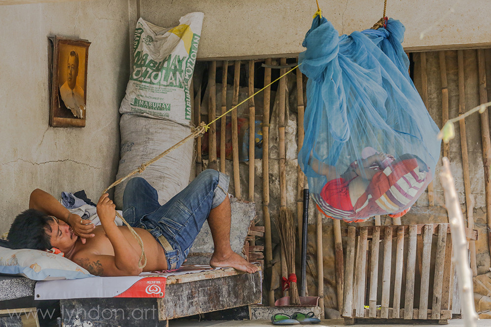 A father rocks his baby in a makeshift cradle inside of their mausoleum home.