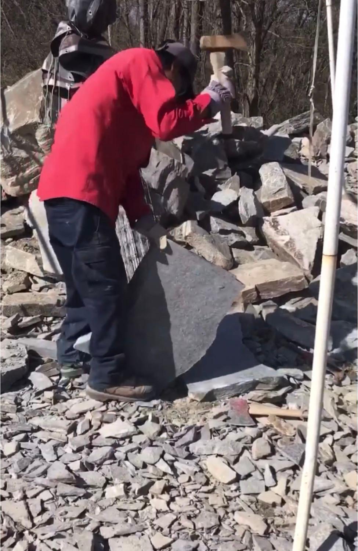 A mason shaping a natural flagstone