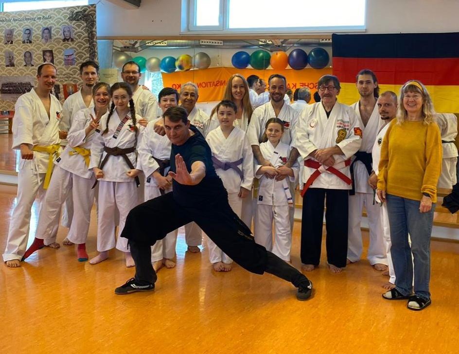 Eine Gruppe von Karatekas - alt und jung - stehen zusammen, im Vordergrund ein Trainer in Schwarz in einer Kungfu-Haltung.