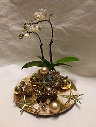 Petite orchidée blanche posé sur une assiette dorée,poivre doré et décorations de Nöel.