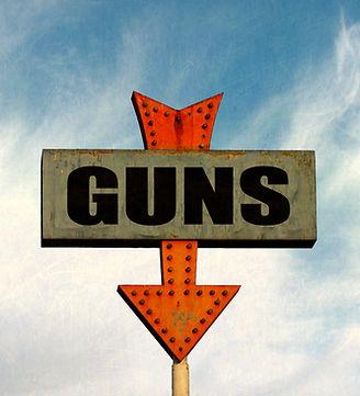 aged and worn vintage of gun shop sign.j