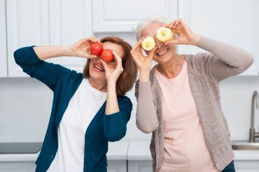 duas mulheres de meia idade com frutas tampando os olhos