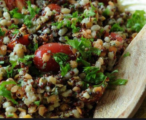 prato com salada de lentilhas, quinua e tomate cereja, ao lado uma colher de pau