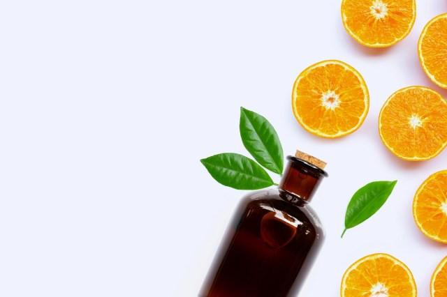 fundo azul com laranjas cortas e frasco grande de óleo essencial