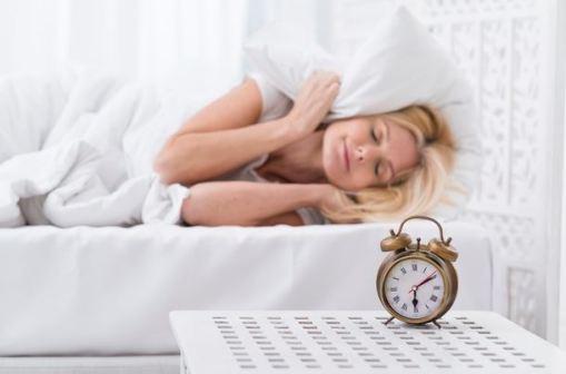 mulher dormindo em cama com lençóis brancos e relógio em uma mesa ao lado