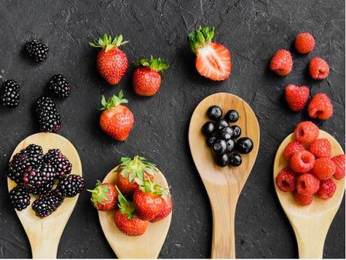fundo preto com frutas vermelhas em colheres de pau