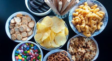 mesa com vários alimentos industrializados: batata chips, salgadinhos, balas, biscoitos