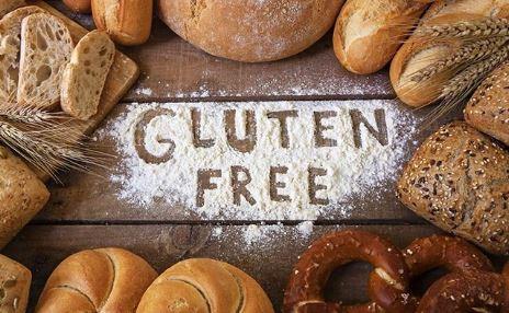 mesa de madeira com mães em volta e farinha de trigo espalhada ao meio com a frase gluten free