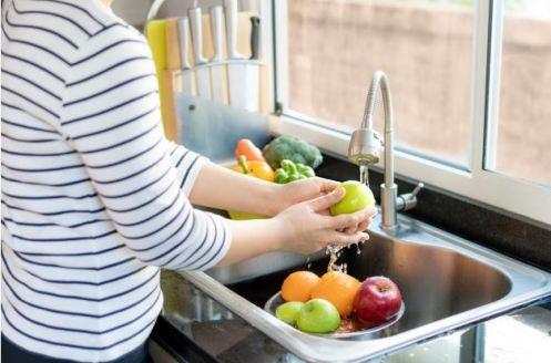 mulher lavando frutas e verduras na pia