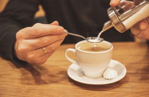 Pessoa adoçando uma xícara de café