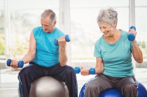 um casal de meia idade fazendo atividade física com pesinhos nas mãos