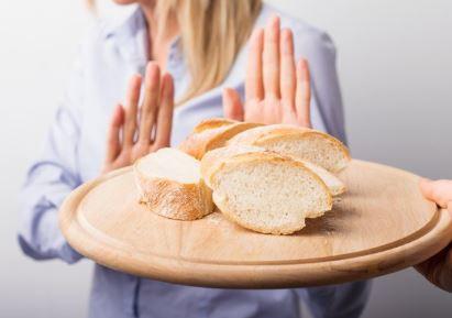 mulher de camisa azul rejeitando uma bandeja redonda de madeira cheia de pães