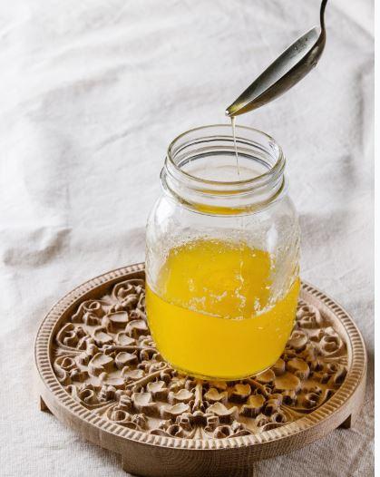 fundo branco, base de cerâmica, pote de vidro sem tampa, colher caindo manteiga no pote