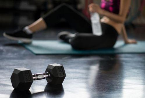 sala de ginastica com peso em primeiro plano e mulher sentada ao fundo com uma garrafa de água