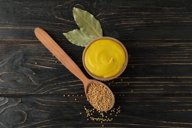 fundo de madeira escura com colher de pau com semente de mostarda e pote com mostarda pronta