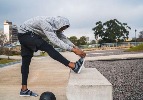 homem negro alogando o corpo em uma pista de corrida durante o dia