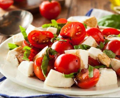 prato de louça branco com tomate cereja, manjericão e queijo branco
