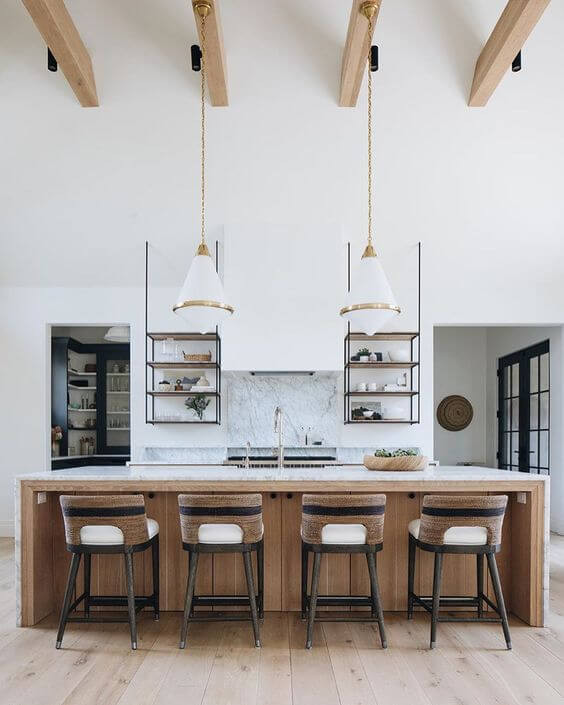 A kitchen. The floors are light timber with a large island bench in the middle of the room. The benchtop is white stone with a mid-tone timber slats underneath. Four black bar stools rest against the bench with leather seats. Behind the bench there is a bench against a white wall with a gold tap visible, on either side there is a walkway for a butler's pantry. Two hanging three-tier shelves are visible on either side of the sink, hanging from the wall. They hold a range of knick-knacks. There are light timber beams on the room with some black downlights attached and two hanging pendant lights which are frosted glass with gold accents and chain.