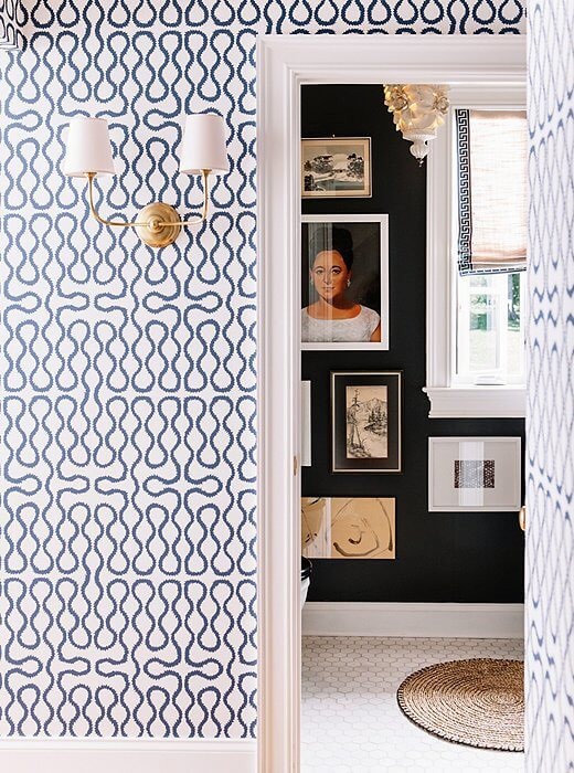 A wall is decorated with patterned blue and white wallpaper. A two-sided gold lamp is attached to the wall with simple white lamp shades. A doorway is visible on the right through which a black painted wall is visible with various paintings hanging on the wall. The floor is beige with a round jute rug